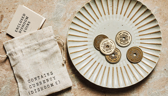 Dishoom Gift Coins on a plate with gift bag